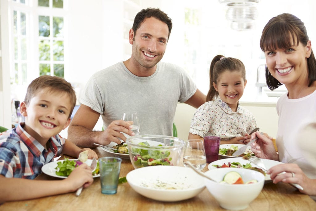 42308717 - family eating meal around kitchen table together